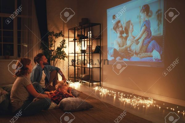 130478035-family-mother-father-and-children-watching-projector-tv-movies-with-popcorn-in-the-evening-at-home